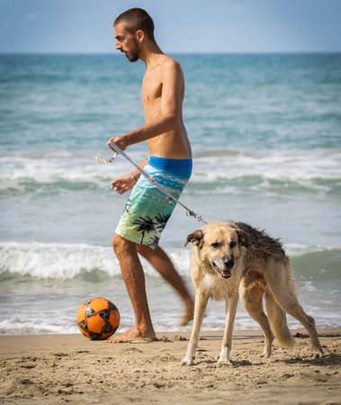 Bufalara, Italy - Septembre 02, 2020, Young man and large shepherd dog playing with bright ball on Bufalara beach in province of Latina in Italy during the second wave of coronavirus (covid 19) Editorial