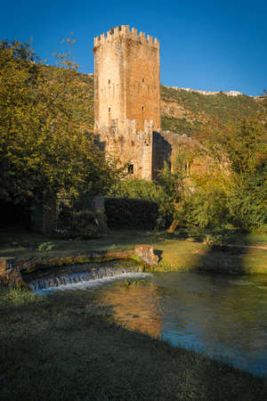 Image of ruins of medieval castle and river with reflections in province of Latina in Italy