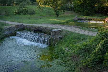 Image of small waterfall on a green river in a park in Italy