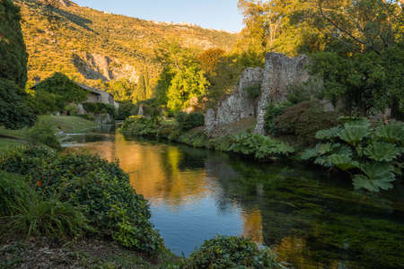image of river and reflections at sunset in Nymph Gardens in province of Latina in Italy Imagens