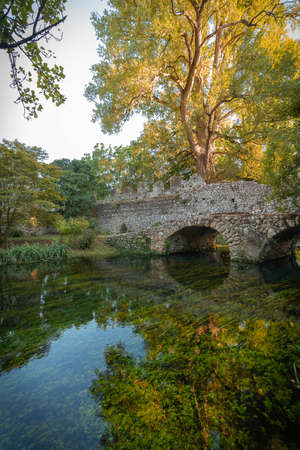 Image of stone bridge with arches and reflection in the water in the Nymph Gardens in the province of Latina in Italy