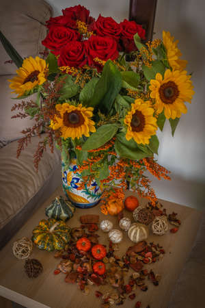 Autumn bouquet with sunflowers and roses and mini pumpkins around in Italy Imagens