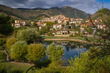 Scenic view of the sunny town of Villalago on the shores of Lake Pio in pre-storm weather in Abruzzo in Italy