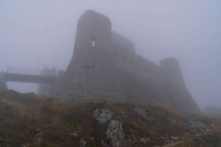 Image of ruins of medieval castle in clouds and fog in Rocca Calasho, Abruzzo, Italy