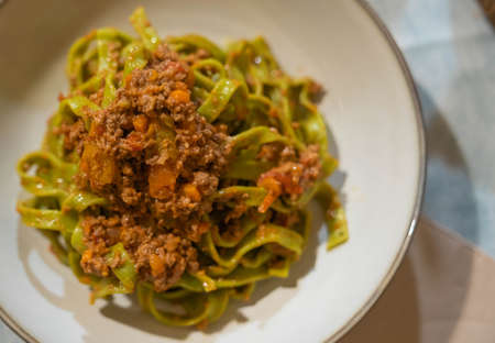 Image of green noodles (tagliatelle) with minced meat and cheese
