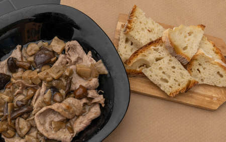 Image of thin cuts of beef cooked with seasonal mushrooms in black plate and homemade bread on wooden board Stock Photo