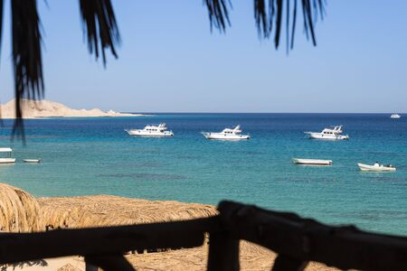view from boardwalk to the beach with some yachts Mahmya island egypt