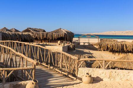 view palm sunshades, beach and some yachts Mahmya island egypt Standard-Bild