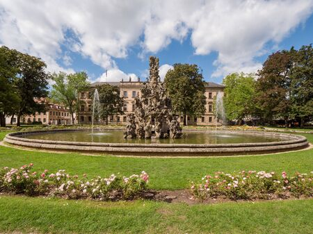 Erlangen, Germany, August 18, 2019: View of the baroque palace garden with fountain and Flowers in the foreground in Erlangen Bavaria, Germany with orangery Editorial