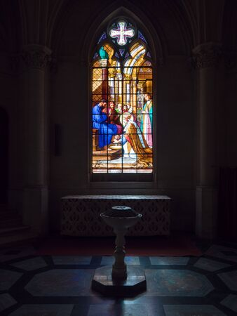 Dreux, France, April 30, 2019: artistic glass windows with baptismal font inside of the Chapel Royal Saint Louis Editorial