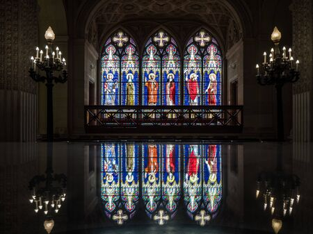 Dreux, France, April 30, 2019: artistic glass windows which are reflected in the lid of a glass showcase inside of the Chapel Royal Saint Louis