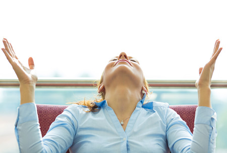 Closeup portrait happy young business woman in blue shirt looking upwards, hands raised in air relaxing on black couch