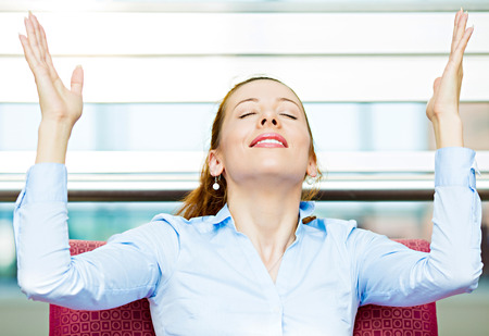 european ethnicity: Closeup portrait happy young business woman in blue shirt looking upwards, hands raised in air relaxing on red couch, armchair