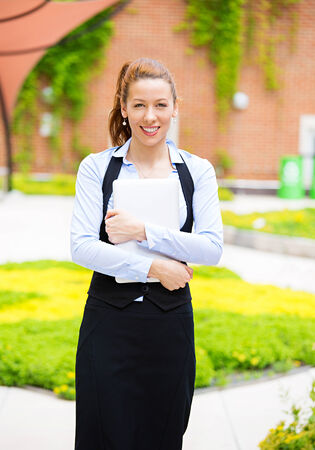 enrolled: Portrait happy, smiling business woman  Summer holidays, education, campus concept  Female student with folders, isolated brick wall