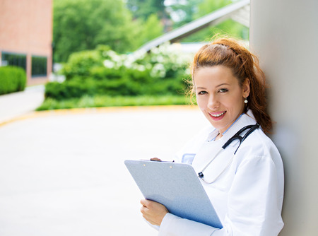 Closeup portrait, young smiling confident female doctor, healthcare professional, isolated outside background hospital backyard  Patient visit health care reform  Positive emotion, facial expression photo