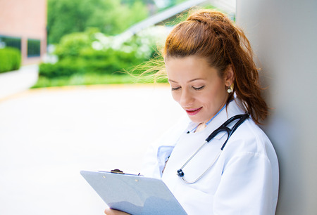 family physician: Closeup portrait, young confident female doctor, healthcare professional reading patient chart isolated background outside hospital, green trees  Patient visit health care  Positive facial expression