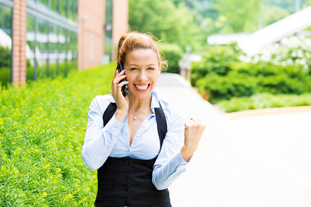 win money: Closeup portrait happy young beautiful woman looking excited, surprised, pumping fists, receiving good news on phone it Stock Photo
