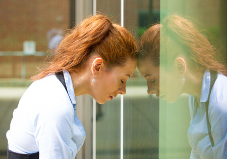 Closeup portrait, unhappy, sad, young business woman, head on window, bothered by mistake having bad headache, isolated background corporate office  Negative human emotion facial expression feeling reaction photo