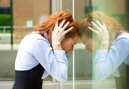 remorse: Closeup portrait unhappy sad young business woman head on window bothered by mistake having bad headache isolated background corporate office  Negative human emotion facial expression feeling reaction