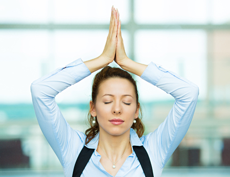 Closeup portrait beautiful hispanic businesswoman relaxing meditating eyes closed, indoors corporate building, office by doing some yoga isolated background windows  Positive emotion facial expression photo