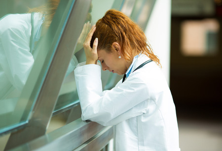 Close-up portret zorgverlener met hoofdpijn, benadrukte, die hoofd tegen het raam glas Verpleegkundige arts met migraine overwerkt, overspannen geïsoleerde achtergrond ziekenhuis hal, gang