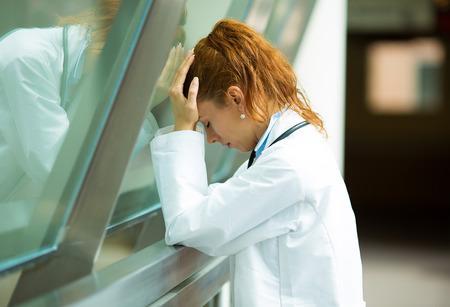 Profesional con dolor de cabeza cuidado de la salud Retrato de detalle, subrayó, sosteniendo la cabeza contra el cristal de la ventana de la enfermera al doctor con la migraña con exceso de trabajo, el fondo aislado estresado sala de hospital, pasillo Foto de archivo - 29190271