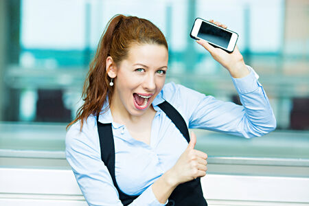 Closeup portrait happy, excited, young, attractive business woman, company employee showing, holding her smart phone, giving thumbs up photo
