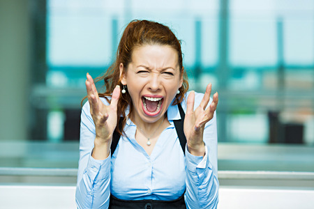 scandal: Closeup portrait mad angry, upset, hostile young businesswoman, worker, furious yelling hands in air Stock Photo