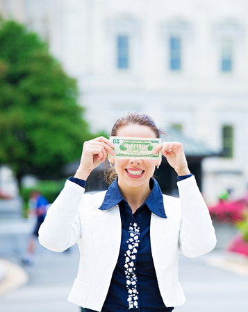 insider trading: Closeup portrait quiet corrupt politician in washington dc, woman holding covering her eyes with dollar bills isolated Capitol building background. Human nature, life perception Greed politics concept