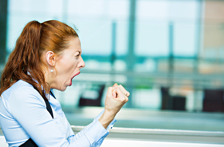 Closeup portrait mad angry, upset, hostile young businesswoman, worker, furious yelling hands, fists in air isolated background corporate office windows. Negative emotions, facial expression, reaction photo