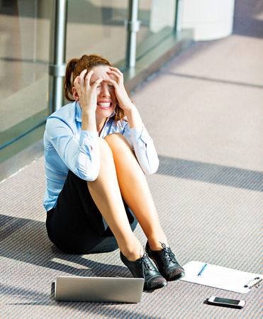 breakup: Closeup portrait young depressed, sad stressed, crying businesswoman sitting on floor in a hall of corporate building, company office, covering her face, with laptop cell phone, documents lying around