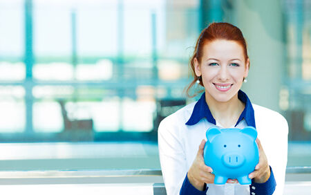 Closeup portrait happy, smiling business woman, bank employee holding piggy bank  isolated background corporate office windows. Financial savings concept. Positive human emotions, facial expressions photo