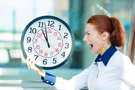 Closeup portrait business woman being late with clock in hands. Concept photo with young businesswoman in hurry running against time, isolated background  corporate office windows. Face expression photo