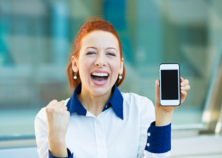customer service phone: Closeup portrait, photo attractive happy smiling young business woman presenting holding smartphone, screen, celebrating successes, pumping fists isolated background corporate office. Positive emotion Stock Photo