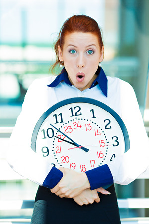 failed plan: Closeup portrait funny looking, anxious business woman, worker, holding wall clock pressured by lack, running out of time, isolated background corporate office windows. Human face expression, emotion Stock Photo