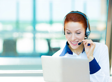 answering call: Closeup portrait young happy successful business woman, customer service representative, call centre worker, operator, support staff speaking with head set isolated background corporate office windows