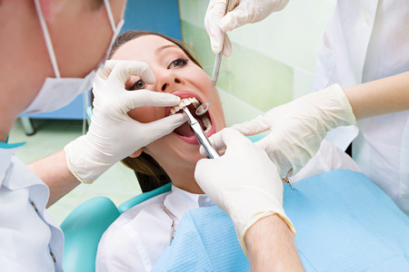 mouth cavity: Closeup portrait dentist, his assistant carrying out thorough examination dental procedure