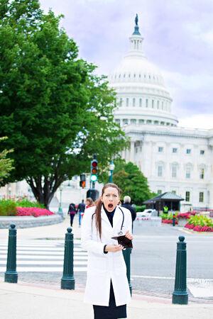 reimbursement: Portrait female health care professional in washington dc, broke woman doctor holding empty wallet isolated Capitol building background. Healthcare reform, medicare reimbursement, obamacare concept