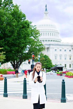 reimbursement: Portrait female health care professional in washington dc, broke woman doctor holding empty wallet isolated Capitol building background. Healthcare reform, medicare reimbursement, obamacare concept