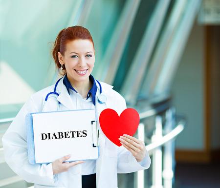 heart disease: Primer retrato sonriente feliz de atención médica profesional femenino, mujer médico de cabecera, el cardiólogo con estetoscopio sosteniendo diabetes muestra, corazón hermoso hospital corredor de fondo. Plan de Paciente