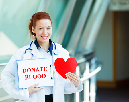 platelets: Closeup portrait happy smiling female health care professional woman doctor, transfusion medicine specialist holding sign donate blood, red heart isolated hospital hallway background. Patient plan