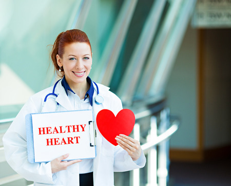 lifestyle disease: Closeup portrait happy smiling female health care professional, woman family doctor, cardiologist with stethoscope holding sign healthy heart, heart isolated hospital hallway background. Patient plan Stock Photo