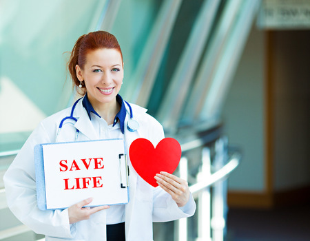 Closeup portrait happy smiling health care professional, woman transplantation medicine doctor, cardiologist with stethoscope holding sign save life, heart isolated hospital hallway background. Stock Photo