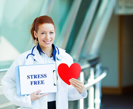 stress free: Closeup portrait happy smiling female health care professional, woman family doctor, cardiologist with stethoscope holding sign stress free, heart isolated hospital hallway background. Patient plan