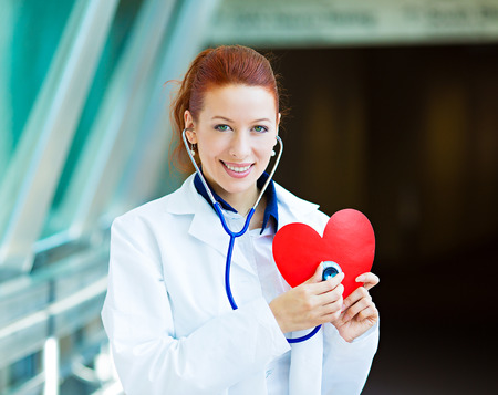 stress test: Closeup portrait smiling cheerful health care professional, pharmacist, dentist, nurse cardiologist doctor with stethoscope, holding listening heart isolated background hospital hallway. Patient visit Stock Photo