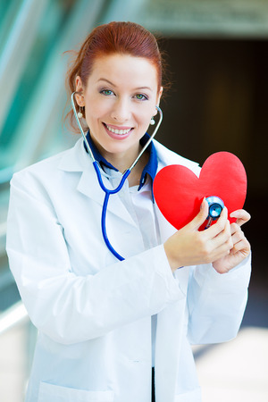 cholesterol free: Closeup portrait smiling cheerful health care professional, pharmacist, dentist, nurse cardiologist doctor with stethoscope, holding listening heart isolated background hospital hallway. Patient visit Stock Photo