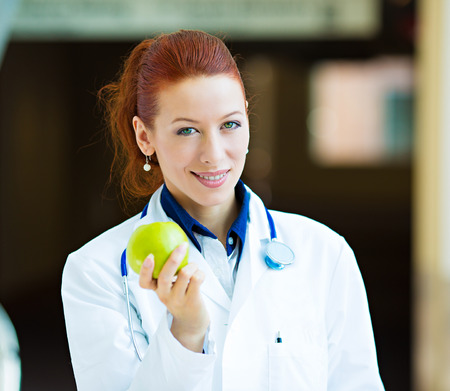 keeps: Closeup portrait smiling happy health care professional, doctor, nurse in lab coat offering green apple, isolated background hospital hallway. A day keeps doctor away concept. Nutrition, healthy diet Stock Photo