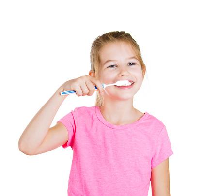 disease prevention: Retrato del primer joven, feliz, sonriente ni�a cepillarse los dientes con pasta de dientes, cepillo de dientes manual aislado fondo blanco. Salud dental oral, prevenci�n de enfermedades. Expresiones faciales positivas