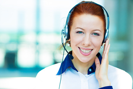 phonecall: Closeup portrait young happy successful business woman, customer service representative, call centre worker, operator, support staff speaking with head set isolated background corporate office windows