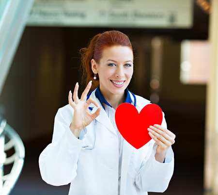 Closeup portrait happy smiling female health care professional, woman family doctor, cardiologist with stethoscope holding red heart, giving ok sign isolated hospital hallway background. Patient plan photo